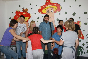 adults and children in circle holding hands in front of cartoon backdrop