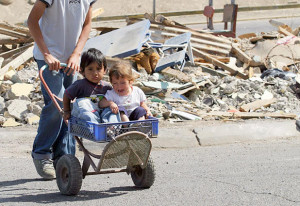 kids in wagon with building ruins